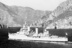 "HMS Gambia, Flagship of Admiral Sir John Edelsten, C in C Mediterranean, entering Marmarice Harbour, Turkey, flying the flag of the C in C. Mediterranean fleet summer cruise, July 1950, and on the Greek island of Skiathos during an exercise known as ""Bandit"". Imperial War Museums A 31692A"