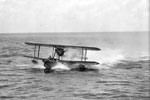A Supermarine Walrus amphibious aircraft from HMS Mauritius lands on the sea after her patrol flight and makes her way towards the cruiser. Imperial War Museums A8910