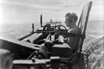One of the pom-pom gun's crew on HMS Warspite, with HMS Formidable in the background. Force A's of the Eastern Fleet return to Kilindini from Colombo. 23 June-2 July 1942. Photo: Lt. D. C. Ouids. Imperial War Museums A 11002