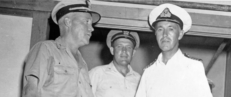 Officers of the U.S. and British Navies on board USS Lunga Point, 11 September 1945. They are (from left to right, front): Rear Admiral Ralph S. Riggs, USN, Commander Cruiser Division 12; Captain R.A.B. Edwards, RN, Commanding Officer, HMS Gambia; and Captain Joseph L. Kane, USN, Chief of Staff for Commander Escort Carrier Forces, Pacific. Collection of Vice Admiral Calvin T. Durgin. Donated by his daughter, Mrs. Phyllis Durgin Sherrill, 1969. Official U.S. Navy Photograph, from the collections of the Naval History and Heritage Command NH 69409.