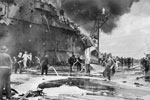 Firefighters busy on board HMS Formidable after a Japanese suicide plane had crashed on the flight deck. The rear part of the aircraft carrier's island can be seen, it is badly scorched whilst the flight deck is covered in foam and water. HMS Formidable was hit by a Kamikaze on May 4 and again on May 9. Imperial War Museums A 29310
