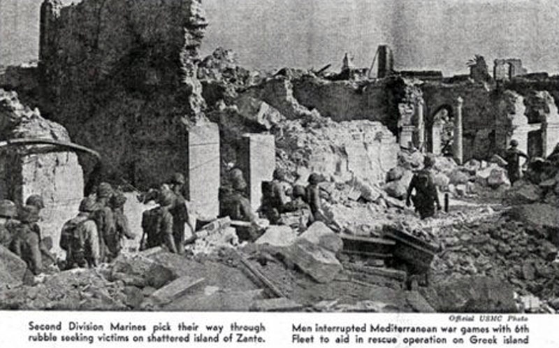 Second Division Marines pick their way through rubble seeking victims on shattered island of Zante. Men interrupted war games with 6th Fleet to aid in rescue operation on Greek island