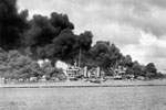 "U.S. Navy light cruiser USS Phoenix (CL-46) steams down the channel off Ford Island's ""Battleship Row,"" past the sunken and burning USS West Virginia (BB-48), at left, and USS Arizona (BB-39), at right, 7 December 1941. U.S. National Archives 12008993"