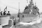 "In November 2001, Ray Holden sent me this photograph taken in 1951 from HMS Liverpool, the ship he served on. He said  ""The picture is of 1st Cruiser Squadron in the Med 1951, the cruiser trying to take our stern off is HMS Kenya."" At first the ship was thought to be HMS Gambia but it is HMS Kenya as there are no director platforms on the front of the bridge. HMS Gambia had platforms that jutted out above B turret."