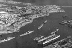 "Grand Harbour, Valletta, Malta, 1955. Photo from Ray Holden. Ray sent me this photo in January 2002. He writes ""The 1st Cruiser Squadron used to tie up on the far side. This picture was taken in 1955 when Sheffield was flagship, that's her second from left. The ship behind is Kenya, this is where Gambia used to tie up behind her flagship which was Liverpool."""