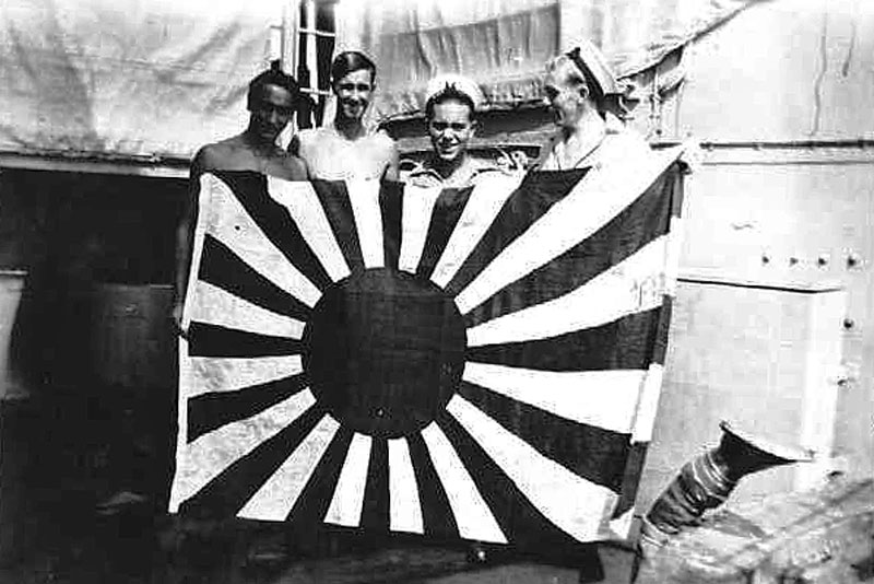 HMNZS Gambia's crew with a captured Japanese flag