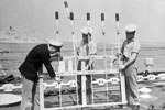 PO Leslie Hirst of Scarborough, Yorkshire with AB's Fred Bidgood of Nuneaton, and Ronald White of Hornecastle, Lincolnshire, preparing rockets on HMS Sheffield for the Review fireworks display. HMS Superb is in the background. Imperial War Museums A32582